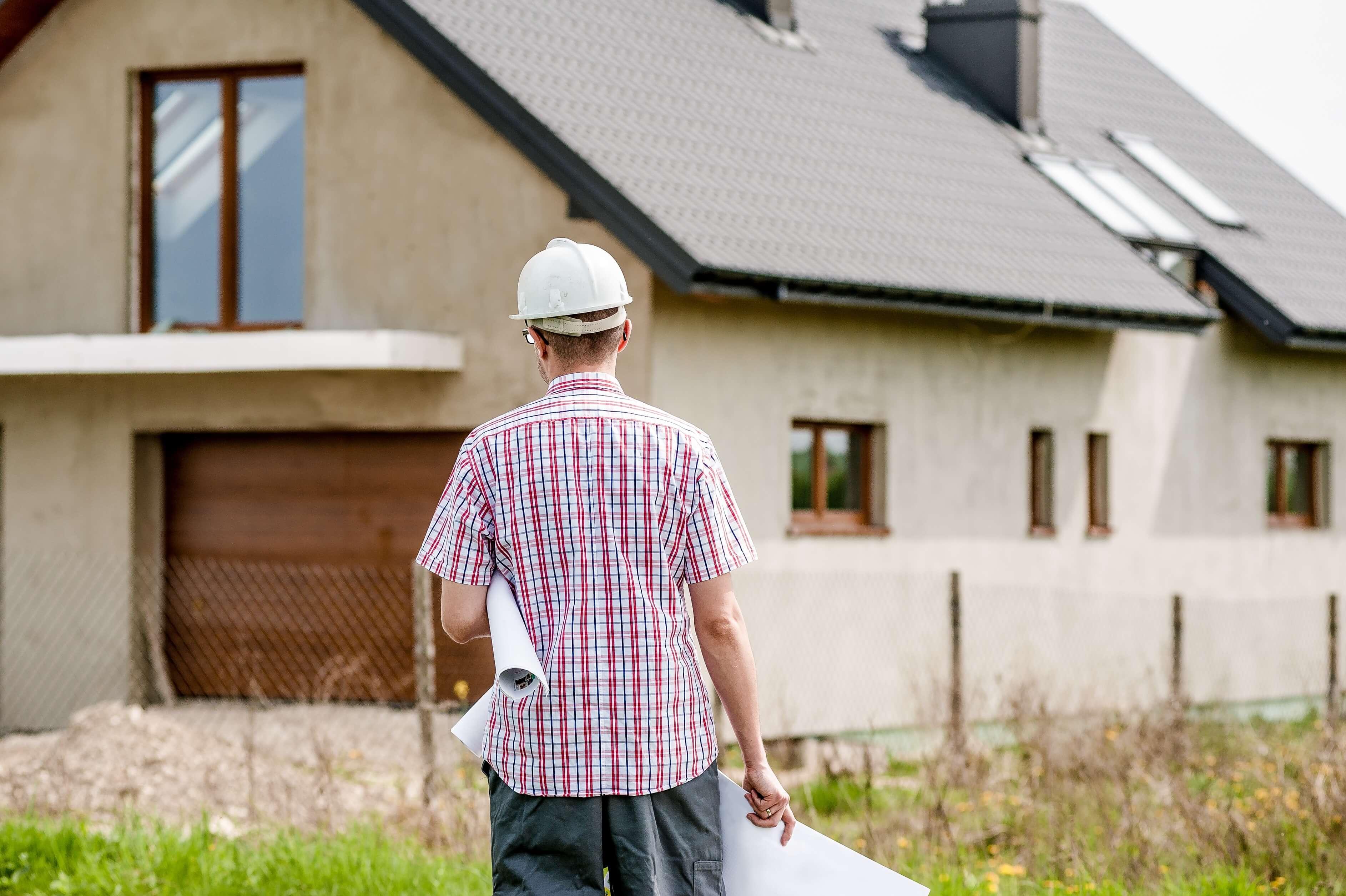 Architekt stojący obok domu